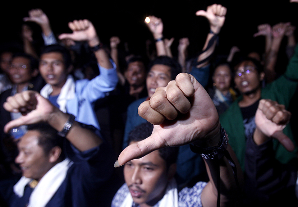 13) Антикоррупционные активисты скандируют лозунги, во время трансляции выступления президента Сусило Бамбанга Юдхойоно в Джакарте, Индонезия. Юдхойоно потребовал от прокуроров снять обвинения в коррупции в отношении двух чиновников, после того, как группа по расследованию обстоятельств заключила, что данные обвинения против должностных лиц, являются необоснованными. (Crack Palinggi/Reuters)