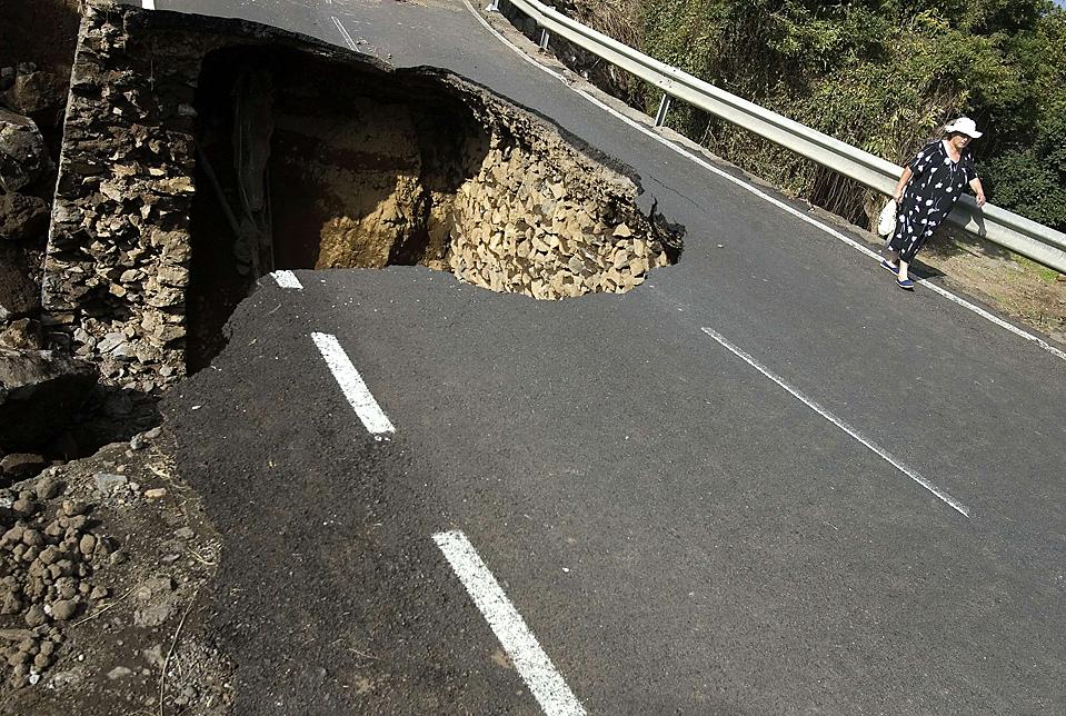 1) Женщина проходит мимо части дорожного покрытия, которое обрушилось после проливных дождей на острове Тенерифе, одном из Канарских островов в Испании. Сильный дождь стал причиной повреждений домов и промышленных объектов. (Santiago Ferrero/Reuters)