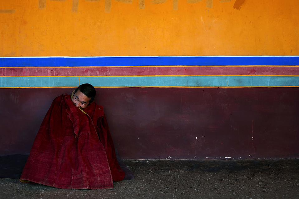 1) Тибетский монах ждет начала религиозных споров с другими монахами в храме Джоканг в Лхасе, Тибет. (Nir Elias/Reuters)
