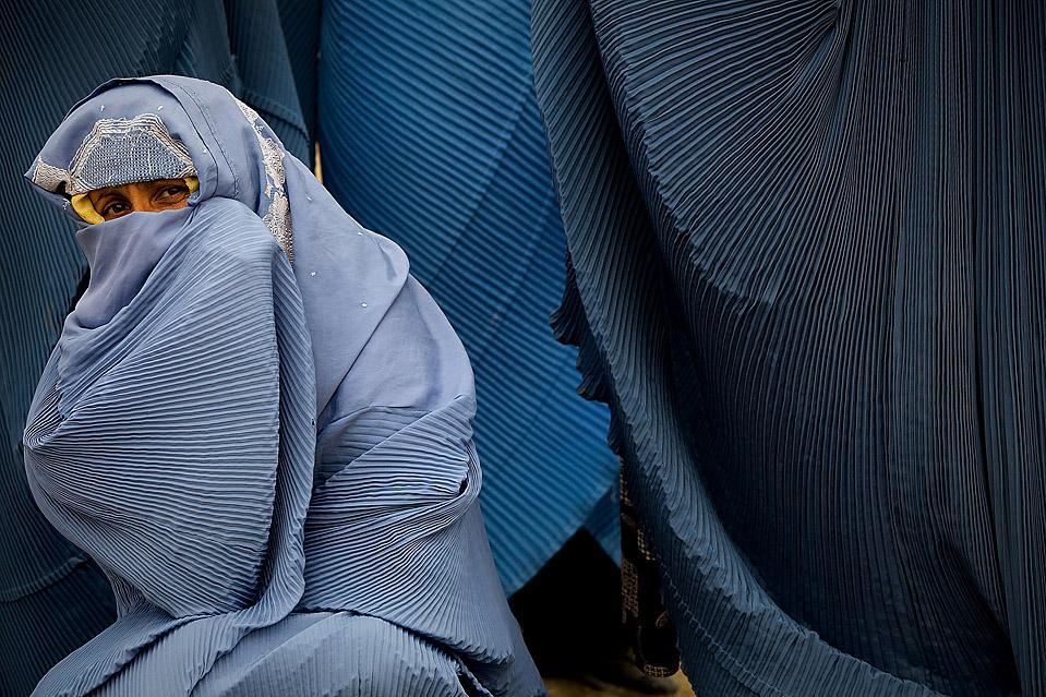 2) Женщина пытается согреться во время ожидания в очереди у пункта распределения продовольствия для вдов в Кабуле. Продовольственные пайки от благотворительной организации «CARE» включают в себя пшеницу, кулинарный жир, соль и бобы. (Paula Bronstein/Getty Images)