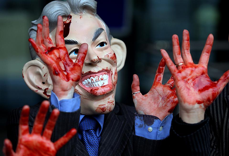 7) Демонстрант с поддельной кровью на руках, в маске бывшего премьер-министра Великобритании Тони Блэра, во время акции протеста, которую устроили перед слушанием о роли Великобритании в иракской войне. Г-н Блэр, как ожидается, выступит во время этого расследования, которое началось в Лондоне во вторник. (Shaun Curry/Agence France-Presse/Getty Images)