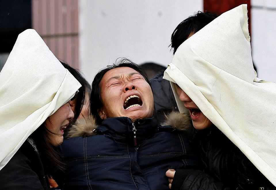 11) Родственники шахтеров, которые погибли в результате взрыва газа в субботу, оплакивают погибших у крематория в городе Хэган, провинция Хэйлунцзян, Китай. Число погибших в  инциденте в понедельник достигло 104. (Aly Song/Reuters)