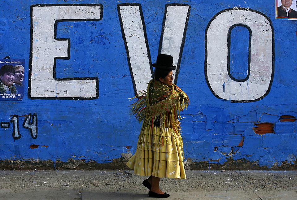 """14) Женщина проходит мимо стены, на которой написано """"Эво"""" в Эль-Альто, Боливия. Боливийцы пойдут на избирательные участки 6 декабря для избрания президента. Одним из основным конкурентов нынешнего президента страны Эво Моралеса является бывший губернатор Манфред Рейес Вилья. (Pilar Olivares/Reuters)"""