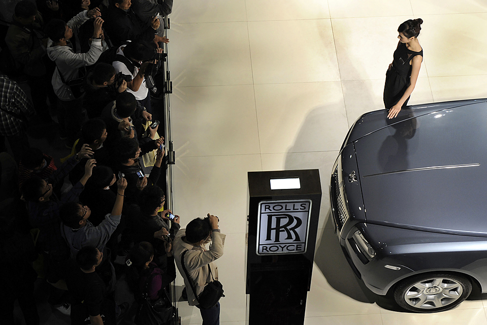 15) Модель позирует рядом с автомобилем Rolls-Royce на международном авто-шоу Гуанчжоу в одноименном китайском городе в провинции Гуандун, Китай, вторник. (Lu Hanxin/Xinhua News Agency via Associated Press)