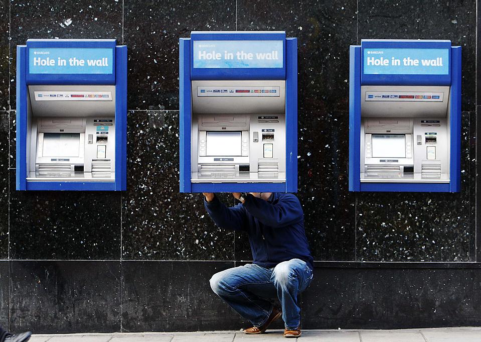 11) Работник ремонтирует банкомат в одном из банков Лондона. Банки Великобритании выиграли судебный процесс  по поводу комиссионных сборов за предоставление кредита, в результате останутся ни с чем сотни тысяч банковских клиентов, которые были намерены потребовать возвращения миллиардов фунтов, взымавшихся, как они считают, несправедливо. (Luke MacGregor/Reuters)