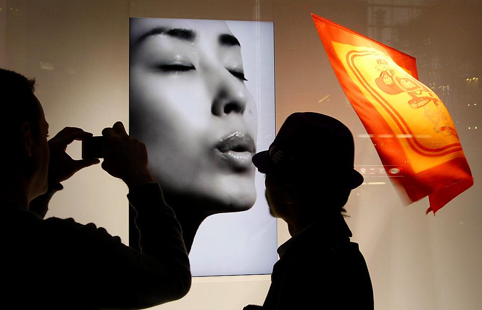 10) Прохожий фотографирует витрину бутика, в торговом районе Гинза в Токио. (Shizuo Kambayashi/Associated Press)