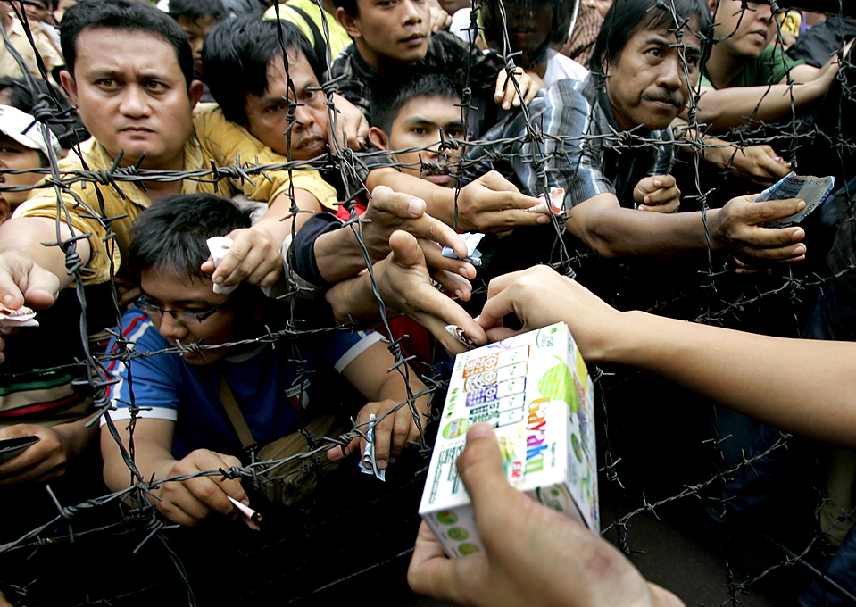 4) Индонезийцы толпятся, чтобы купить мобильные телефоны по сниженным ценам у здания торгового центра в Джакарте, Индонезия. Телефоны продавались по цене около $ 10. (Irwin Fedriansyah/Associated Press)