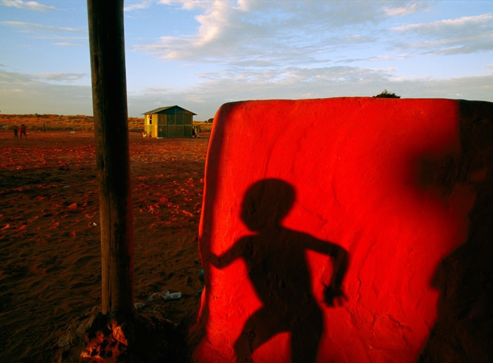 11. Тень бегущего бушменского мальчика на красной стене в Велкоме, Южная Африка. Как и многие бушмены, этот мальчик и его родственник живут, как поселенцы вот уже два десятилетия, забытые африканским правительством. (Chris Johns)