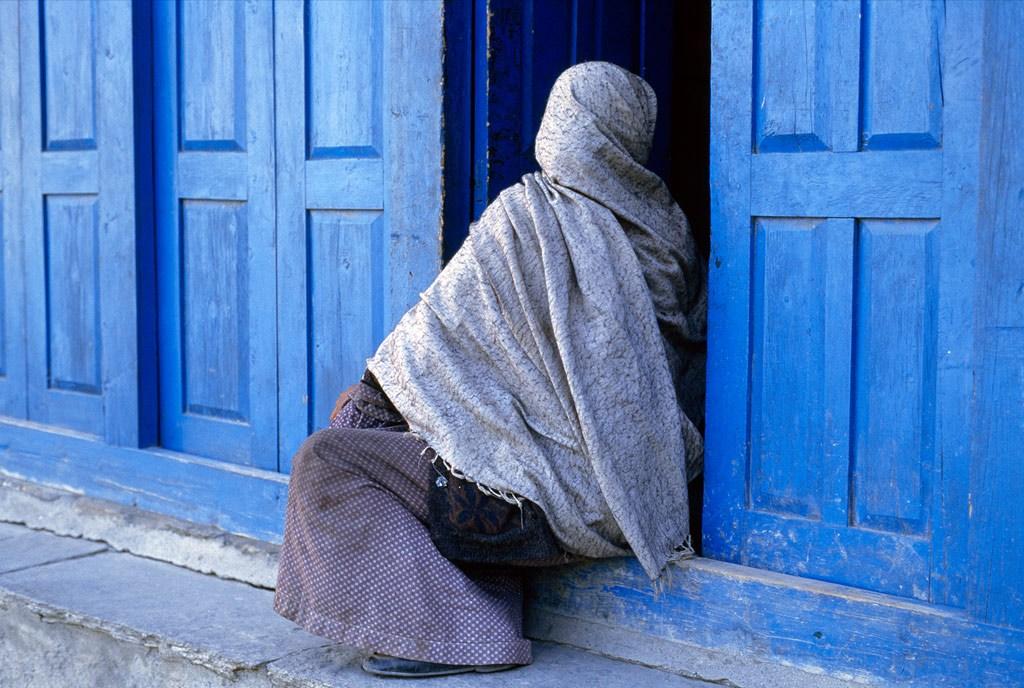 11. Непальская женщина, с ног до головы замотанная в голубоватую ткань, остановилась, чтобы отдохнуть в красочном проеме двери. Снимок сделан в одном из небольших городков в Непальском регионе Анапурна. (Steve McCurry)