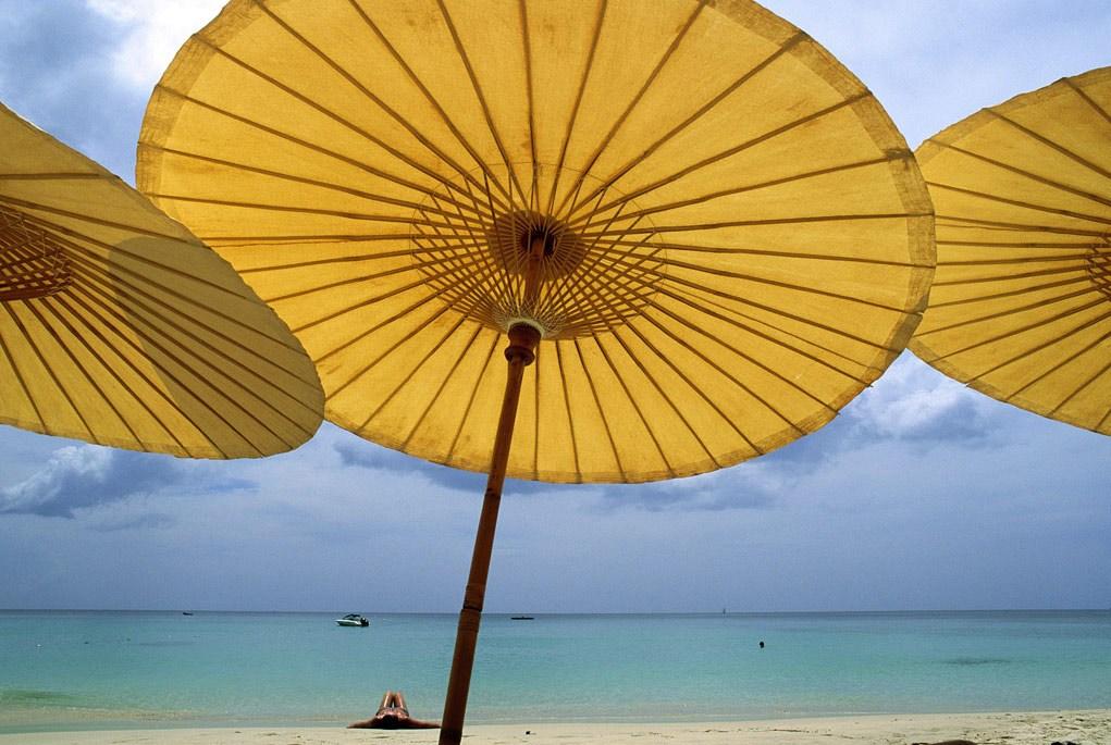 11. Желтые пляжные зонтики выстроились в линию на песке у отеля острова Пхукет, Таиланд. Остров привлекает многих иностранных туристов своими успокаивающими пляжами, кристально чистыми водами и тайской гостеприимностью. (Jodi Cobb)