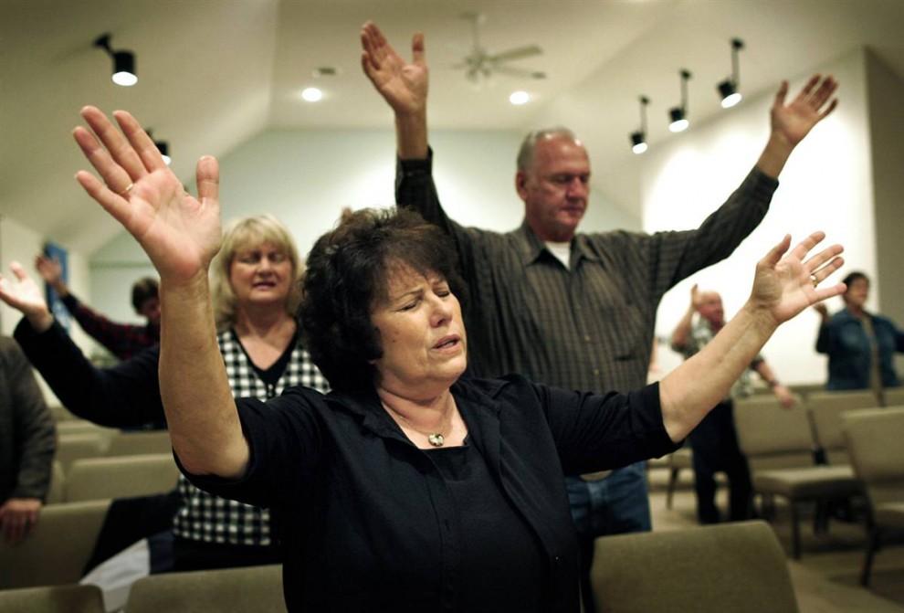 12. Пенни Андерхилл поднимает руки во время молитвы в нонконформистской церкви братства пятидесятников в Мюррее, штат Кентукки. Ее муж Шелби ведет собрание братства. (Brooke Grace/2009 Mountain Workshops)