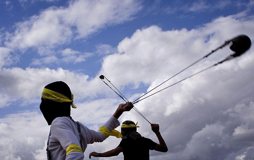 12) Палестинские демонстранты с помощью пращей бросают камни в израильских солдат в ходе демонстрации протеста против израильского разделительного барьера на Западном берегу в поселке Нилин, возле Рамаллы. (Tara Todras-Whitehill/Associated Press)