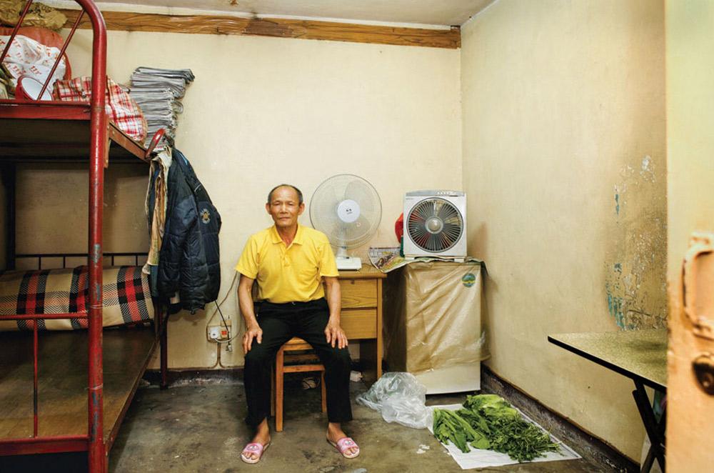 7. Чану Кам Хуню 68 лет, 15 из них он прожил в общежитии Шек Кип Мей. Он торгует техникой. В этом месте ему больше всего нравится «хорошая атмосфера». (Michael Wolf/ New York Times Lens)