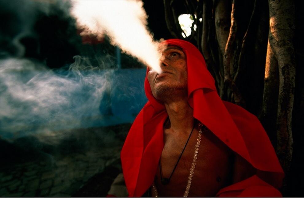 12. Индусский аскет, или садху, в ярко-красном одеянии курит под священным фикусом у храма в Мумбаи. Садху посвящают себя духовной жизни, у них практически нет личных вещей, живут они на подаяние. (Michael Yamashita)