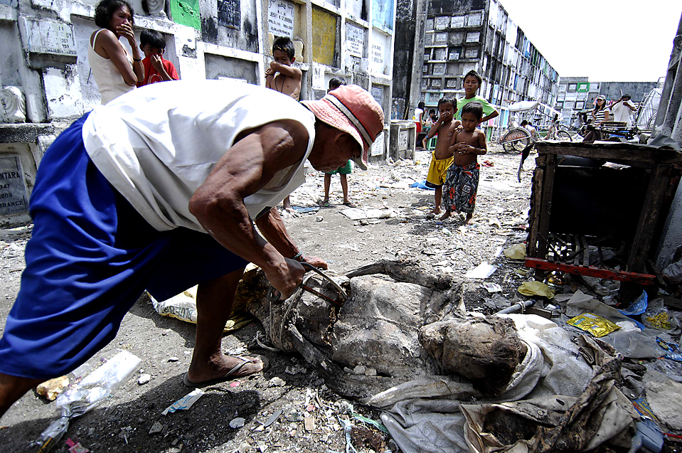 13) Дети наблюдают за тем, как смотритель кладбища с помощью пилы распиливает мумифицированный труп на три части, чтобы похоронить его в меньшей могиле. Снимок сделан в городе Новатос, Филиппины, пятница. В день Всех Святых, в воскресенье миллионы христиан отправились на кладбища чтобы навестить своих почивших родственников. (Noel Celis/Agence France-Presse/Getty Images)