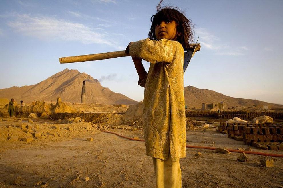 16. 5-летняя Гульсима держит лопату во время работы на заводе. Кирпичные заводы в Кабуле – источник экономического процветания. Земля сухая и бесплодная, что идеально подходит для изготовления кирпичей, предлагая работу практически круглый год. Однако на кирпичных заводах часто эксплуатируют детский труд. (Paula Bronstein, Getty Images)