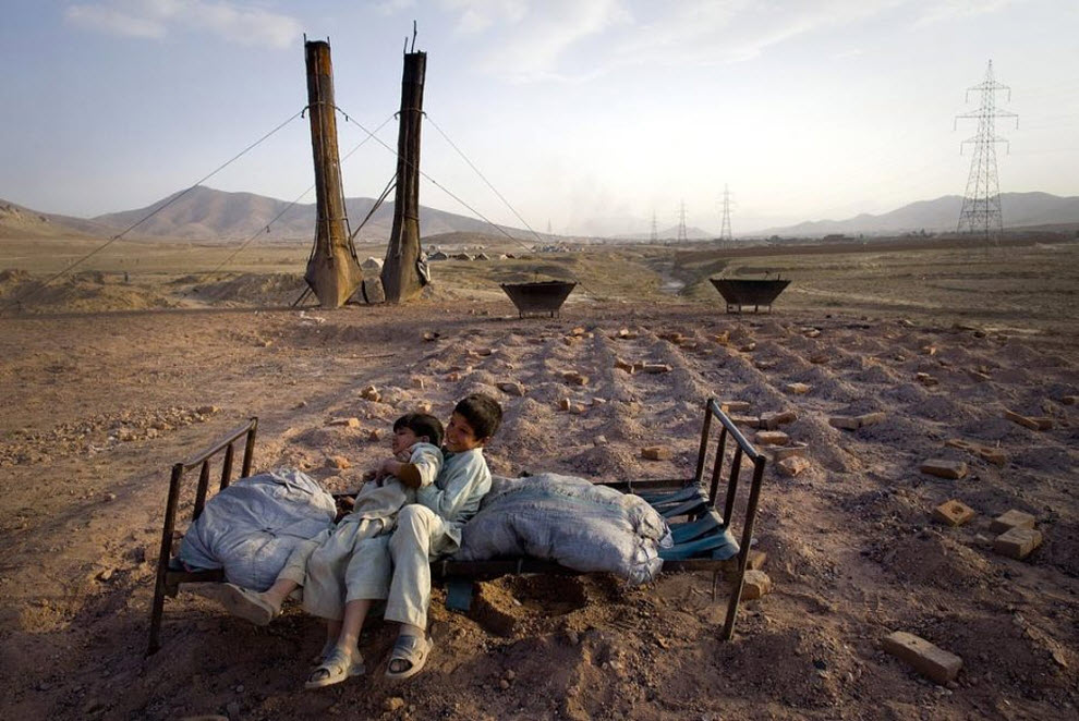 14. Афганские дети отдыхают на кровати на кирпичном заводе, сохраняя тепло от печи для обжига кирпичей. (Paula Bronstein, Getty Images)