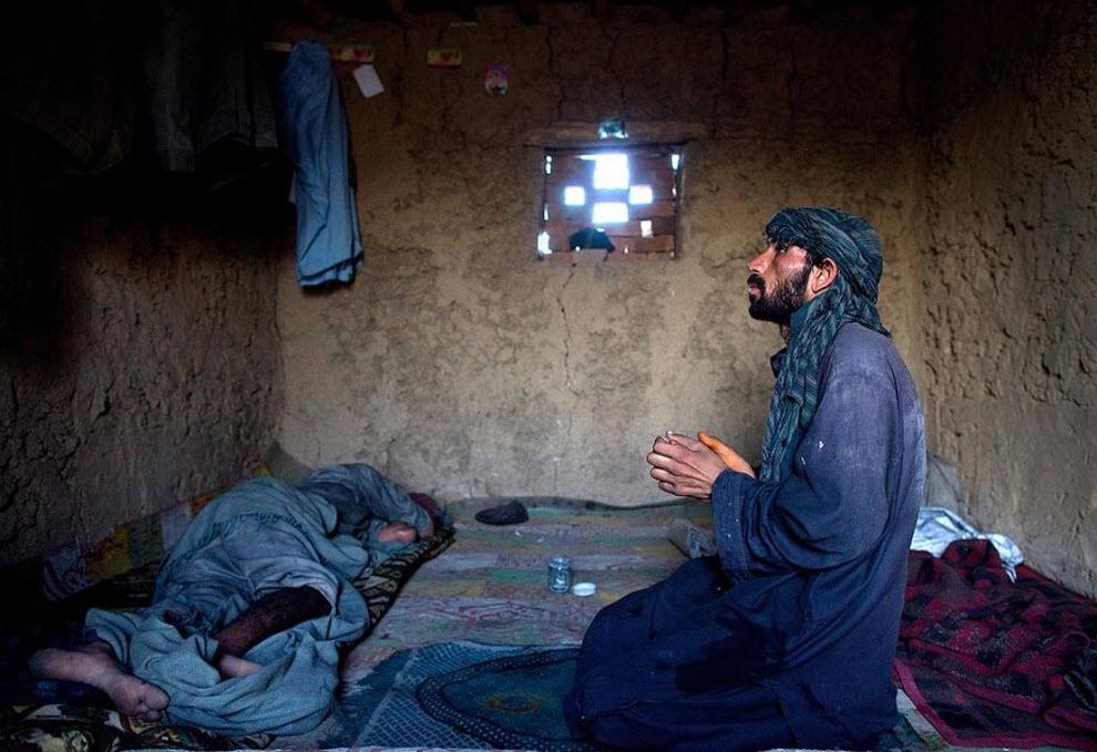 15. Рабочий кирпичного завода молится в своей хижине, пока другой рабочий спит. (Paula Bronstein, Getty Images)