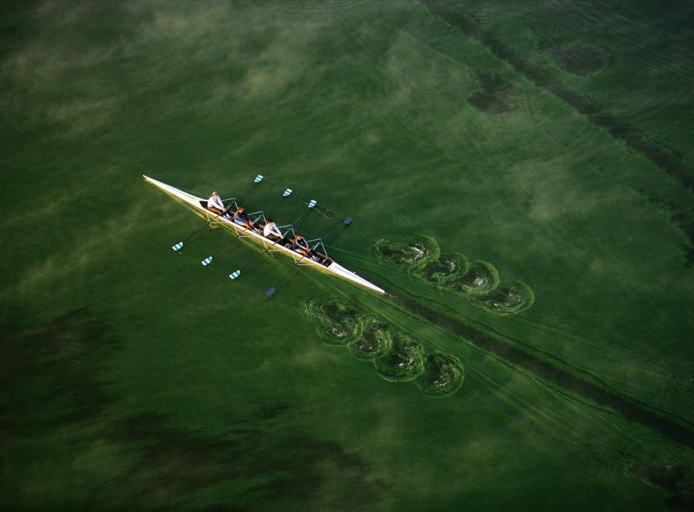 16. Команда гребцов использует синхронную силу, чтобы проплыть по зеленым водам с тонким слоем водорослей во время утренней тренировки на озере Аматитлан, Гватемала. (Bobby Haas)