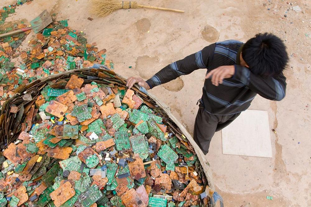 15) Рабочий во время сортировки электронных отходов.