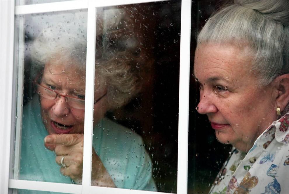 16. Пэт Миллер (слева) И Донна Херндон (справа) решили переждать дождь в доме Миллер и теперь смотрят на ее сад. «Кто-то любит кошек. Кто-то собак, - говорит муж Донны. – А моя жена любит людей». У 67-летней Донны Херндон нежное сердце, она не может отказать нуждающимся в помощи людям. Она уже давно является добровольцем и лидером сообщества, выполняющим самые разные обязанности, с одним общим знаменателем – она всегда помогает другим. (Britney Mcintosh/2009 Mountain Workshops)