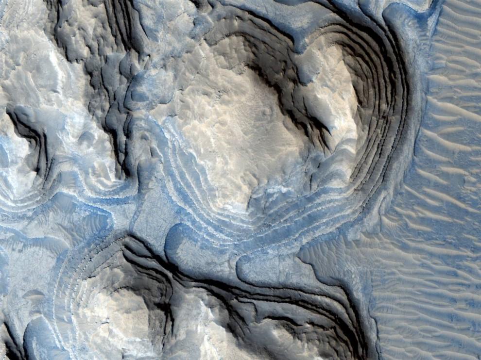 16. На этом снимке с цветной маркировкой региона Марса, известного как Терра Аравия, выступают различные слои камня. Снимок был сделан станцией «Mars Reconnaissance Orbiter» и опубликован 18 ноября. Ученые считают, что на фотография может продемонстрировать, как различные слои осадков образовывались во время климатических циклов на Марсе. (NASA/JPL/University of Arizona)
