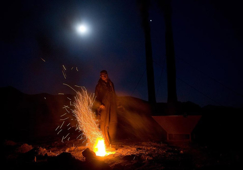 1. Афганский рабочий кирпичного завода подбрасывает уголь в печь для обжига кирпичей, чтобы огонь горел всю ночь. (Paula Bronstein, Getty Images)