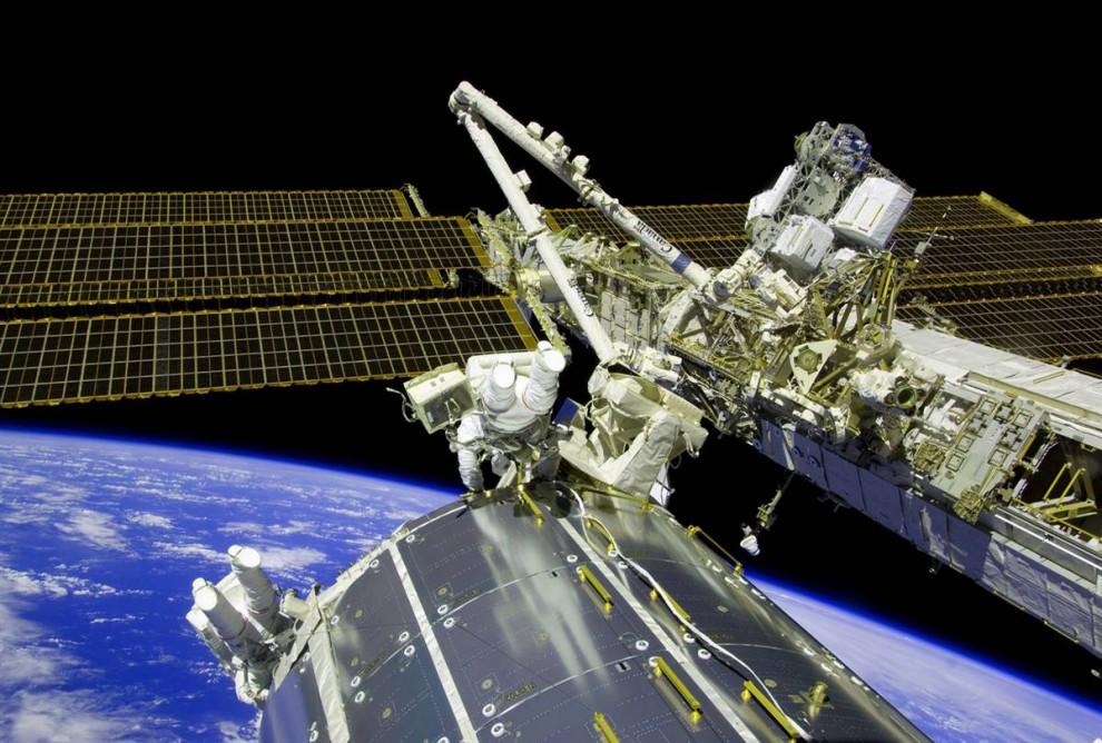 17. Астронавты «Атлантиса» Майк Форман (в центре) и Рэнди Бресник (внизу слева) выполняют задачи техобслуживания Международной космической станции на фоне горизонта Земли 21 ноября. (NASA via AFP - Getty Images)