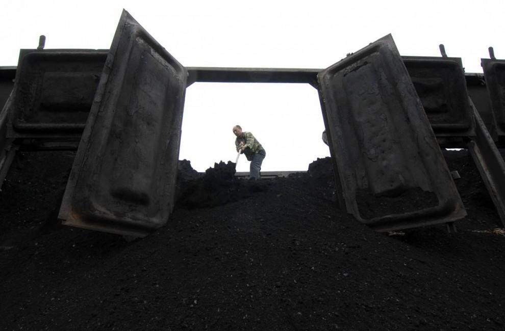 17. Рабочий разгружает уголь с поезда в Ксиангфане, Китай. Страна по-прежнему зависит от электростанций на угле – главном источнике выбросов углекислого газа. (Stringer/china / REUTERS)