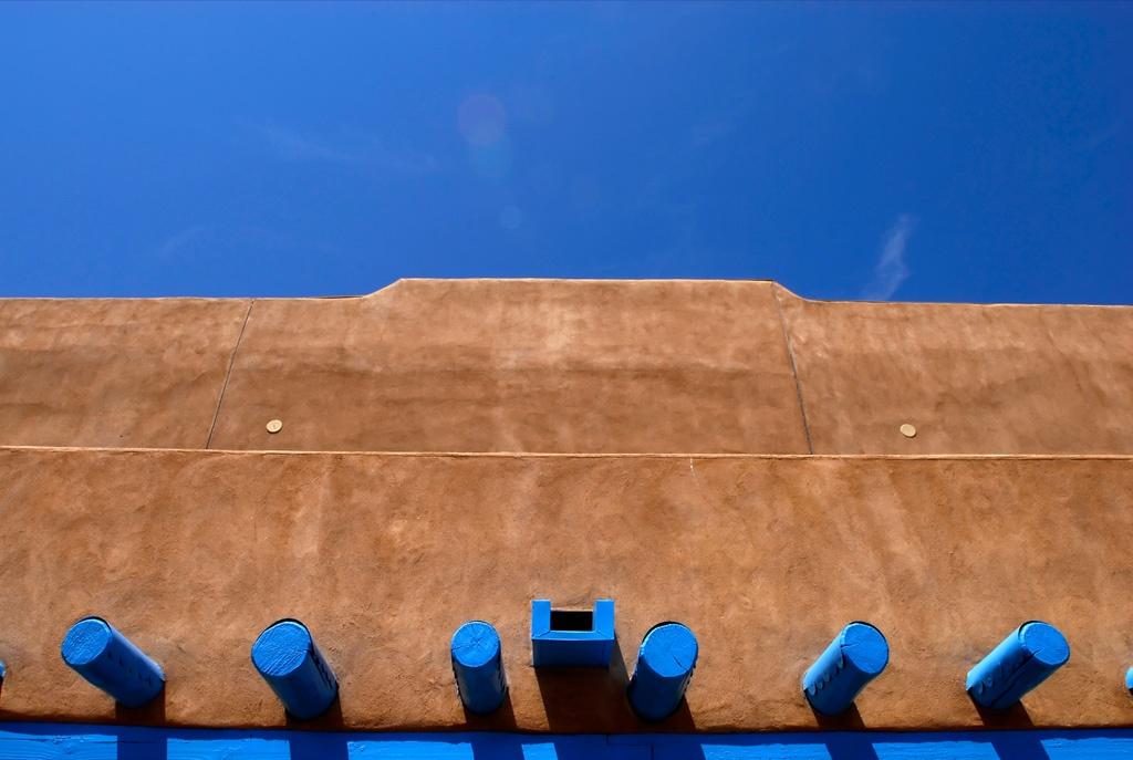 17. Голубое небо и балки обрамляют коричневый глиняный дом в Таосе, Нью-Мехико. Сделанные из самой земли, эти здания обычно строились индейцами. (Raul Touzon)