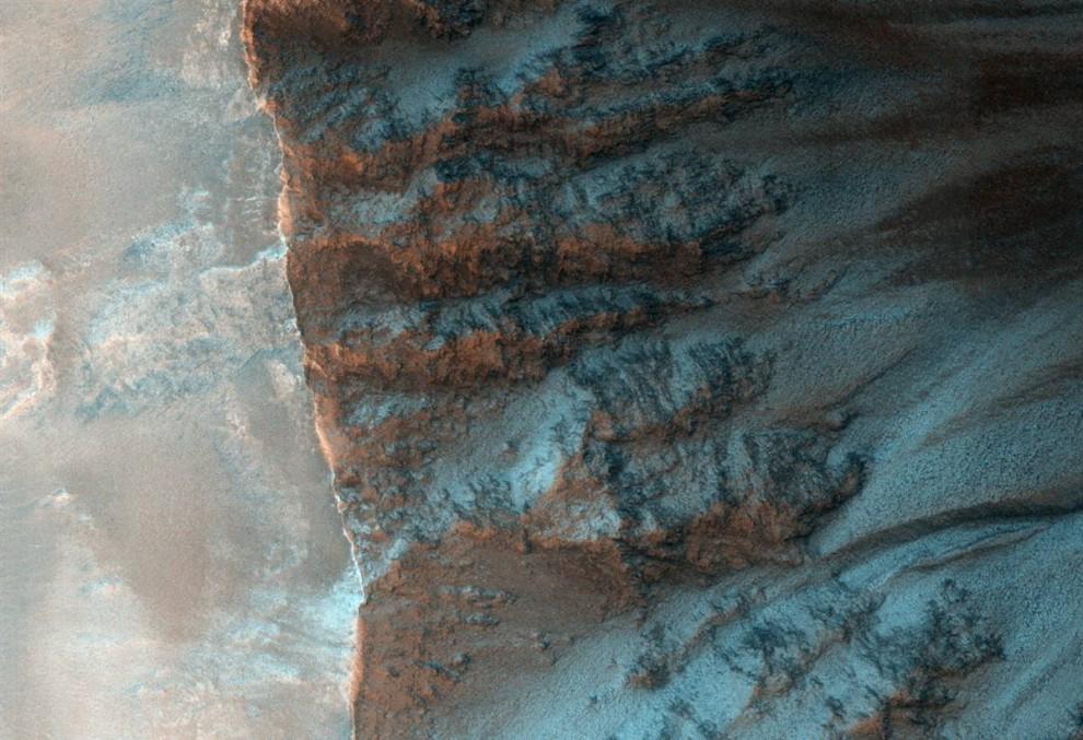 18. На этом снимке, сделанном станцией «Mars Reconnaissance Orbiter» и опубликованном 18 ноября, видны рытвины, идущие вдоль края кратера в северном полушарии Красной Планеты. Ученые полагают, что, по крайней мере, некоторые из марсианских рытвин были созданы появлением воды из-под поверхности. (NASA/JPL/University of Arizona)