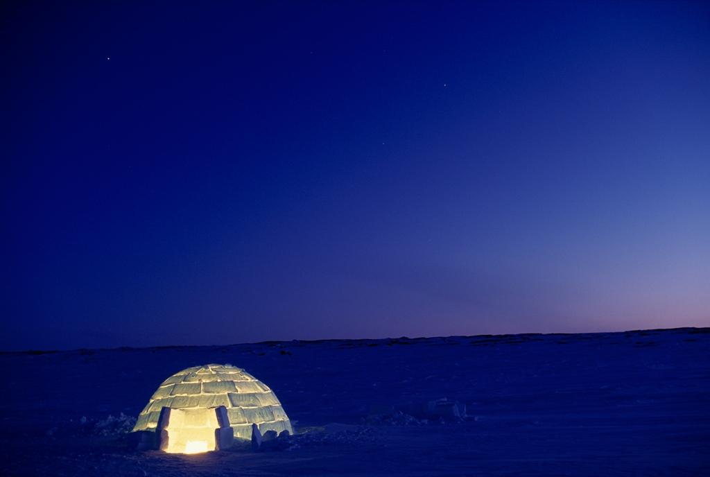 18. Уютное иглу освещает суровый пейзаж холодной ночью в Канадской Арктике. Эти временные жилища обычно использовались местным населением в суровой Арктике Северной Америки. (Norbert Rosing)