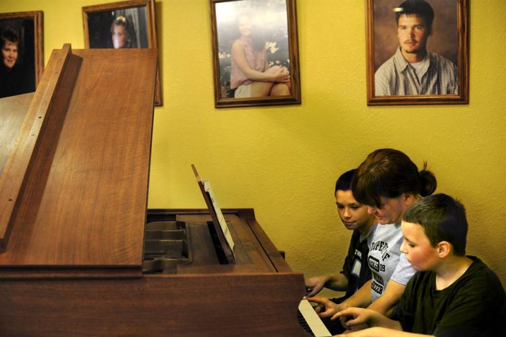 18. Директор старшей школы Мюррея Тереза Спид играет на пианино со своими сыновьями – 10-летним Томасом (слева) и 9-летним Джейденом (справа). Они с мужем Джозефом женаты уже 17 лет, и в их семье 12 детей. Семь из них они усыновили. (Rebecca Barnett/2009 Mountain Workshops)