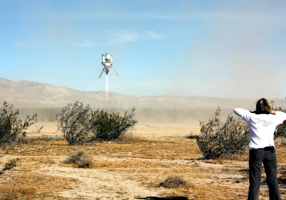 20. Ракета «Xoie» компании «Masten Space Systems» поднимается над пустыней Мохаве в Калифорнии во время полета 30 октября, который принес компании один миллион долларов в конкурсе «Northrop Grumman Lunar Lander Challenge». НАСА установила приз в один миллион долларов, чтобы поддержать технологии развития новых космических летательных аппаратов. (NGLLC / X Prize Foundation)