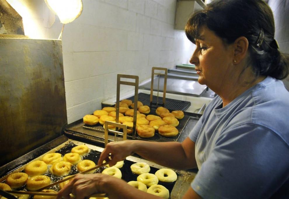 23. 50-летняя Тереза Баст лепит пончики и, дав им подняться, жарит их на противне, после чего покрывает сделанной дома глазурью. «Нет ничего лучше горячего пончика со свежей глазурью», - говорит она. (Delayna Earley/2009 Mountain Workshops)