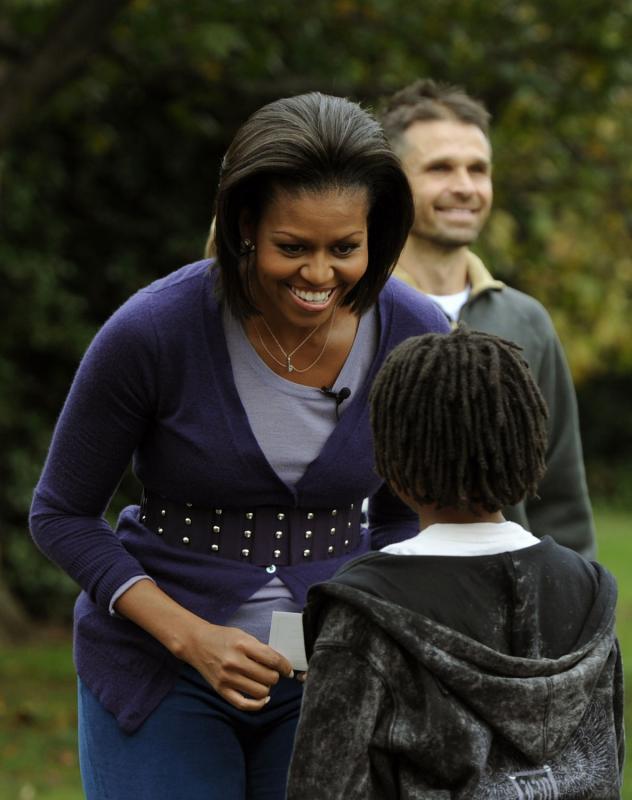 26. Первая леди Мишель Обама приветствует прибывших учеников начальных школ Банкрофт и Кимболл на уборку урожая в Белом Доме в Вашингтоне 29 октября 2009 года. (UPI/Alexis C. Glenn0