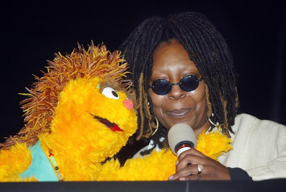 27. 26 ноября 2002: актриса Вупи Голдберг и Ками – персонаж южноафриканской версии «Улицы Сезам» с положительной реакцией на ВИЧ – обнимаются на встрече в городском муниципалитете по случаю Всемирного дня борьбы со СПИДом в Нью-Йорке.