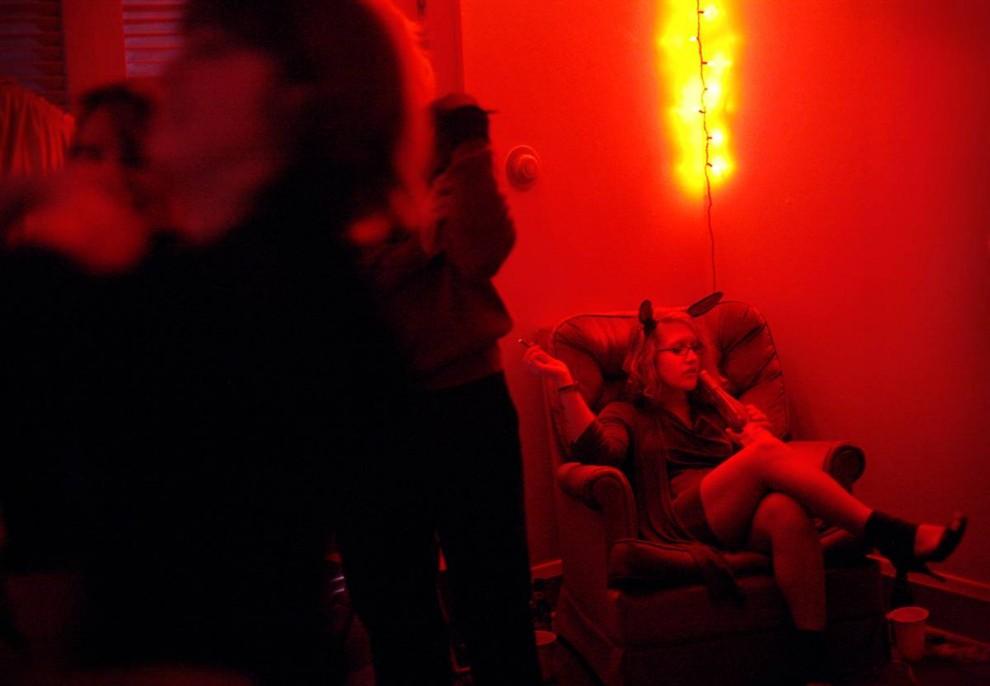 28. Лили Бурланд курит сигареты на вечеринке в честь Хэллоуина в своем доме. Бурланд учится в государственном университете Мюррея. Она решила устроить вечеринку для Организации студентов отделения искусства в университете. (Allie Garza/2009 Mountain Workshops)