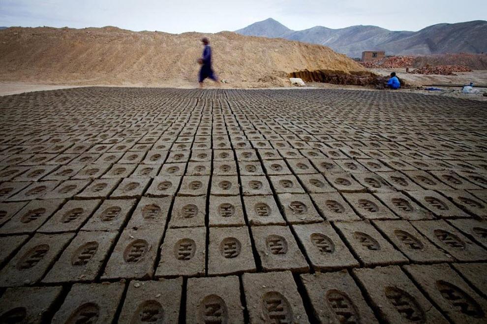 3. Афганский рабочий завода проходит мимо сушащихся кирпичей 6 ноября в Кабуле. Несколько лет назад все заводы перешли с дерева на уголь, что только усугубило ситуацию с загрязнением окружающей среды. По этой причине заводы перенесли за пределы города. В месяц рабочие зарабатывают в среднем 200-300 долларов. За 1000 кирпичей завод получает примерно 45. (Paula Bronstein, Getty Images)