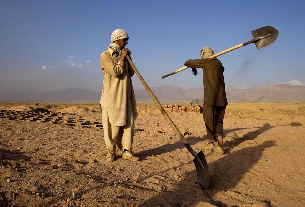 4. Афганский рабочий готовится засыпать песок в форму для кирпича на кирпичном заводе компании «Sadat Ltd. Brick». (Paula Bronstein, Getty Images)
