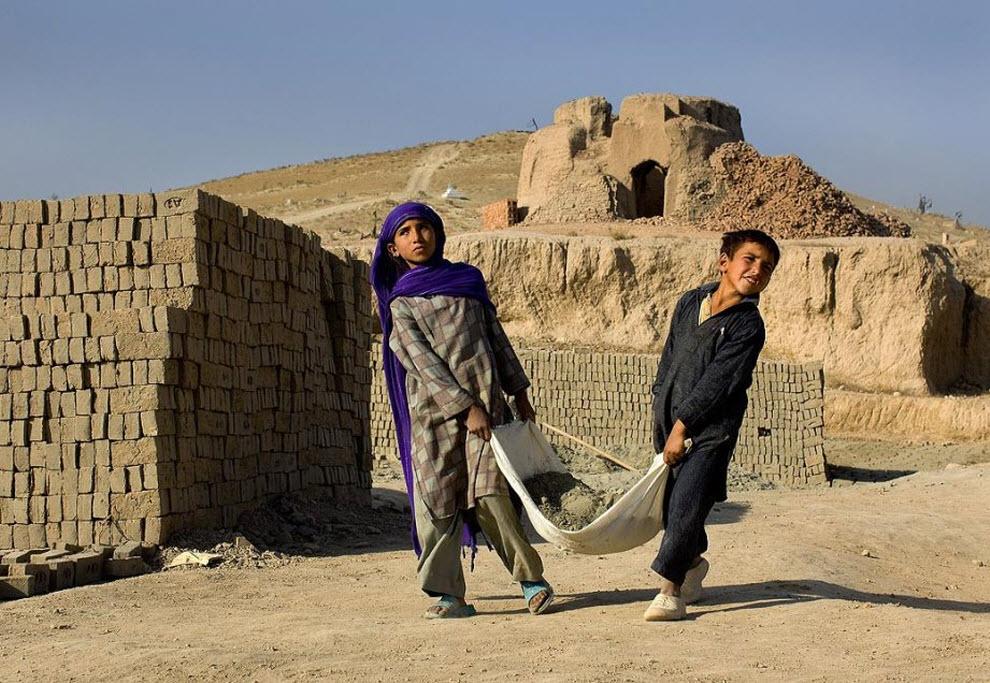 5. 8-летняя Шаджахан и ее брат 6-летний Саджерхан несут тяжелый мешок глины для изготовления кирпичей. (Paula Bronstein, Getty Images)