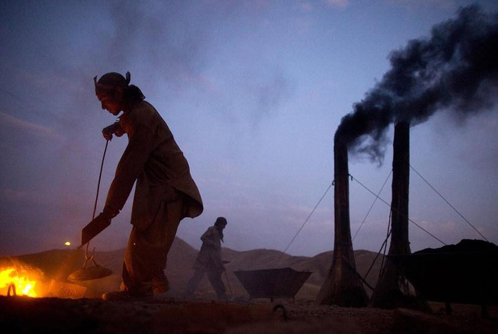 7. Афганский рабочий засыпает лопатой уголь в печь для обжига кирпича. (Paula Bronstein, Getty Images)