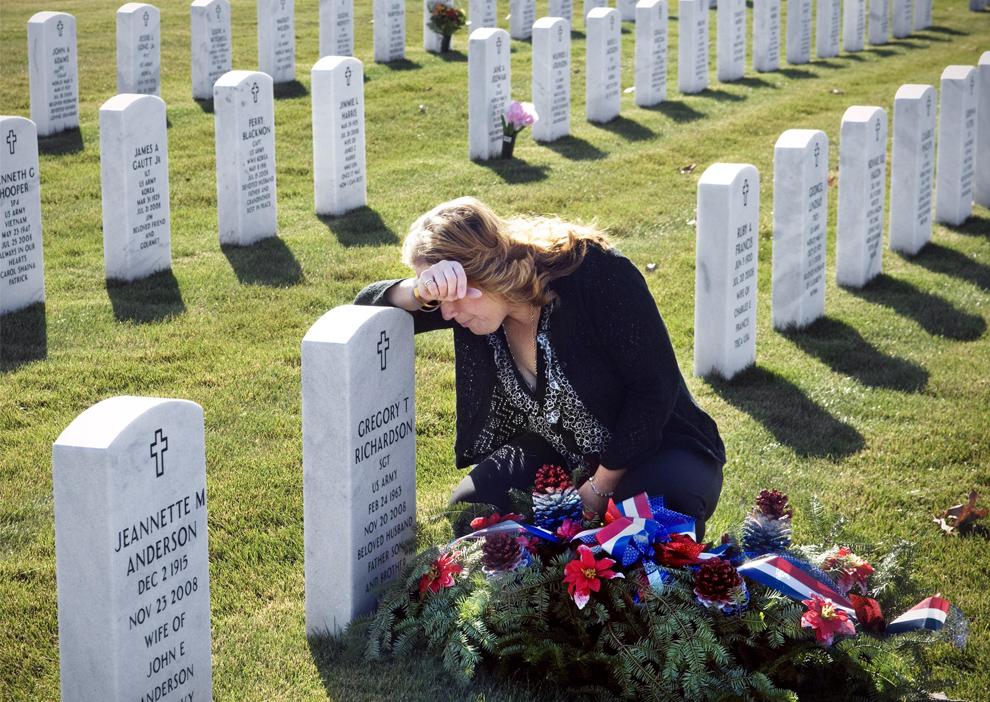 2. Кимберли Ричардсон из Генеси, штат Мичиган, у надгробия своего супруга сержанта армии США Грегори Т. Ричардсона во время посещения его могилы в День Ветеранов в среду 11 ноября 2009 года на Национальном кладбище Грейт Лейкс в Холли, штат Мичиган. (AP Photo/The Flint Journal, Ryan Garza)