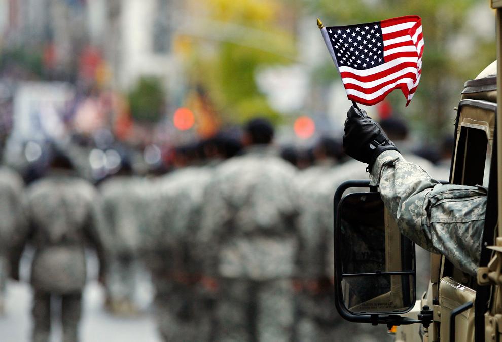 3. Военнослужащий армии США размахивает американским флагом на пятой Авеню во время парада в честь Дня Ветеранов в Нью-Йорке 11 ноября 2009 года. (REUTERS/Shannon Stapleton)
