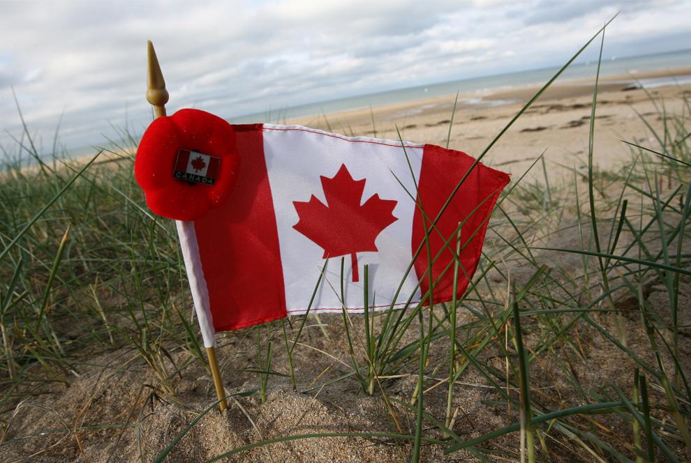 4. Канадский флаг недалеко от пляжа Джуно (одного из мест высадки союзных войск во время Нормандской операции) на церемонии в честь ветеранов Второй мировой войны недалеко от Каена, Нормандия, в среду 11 ноября 2009 года. (AP Photo/David Vincent)