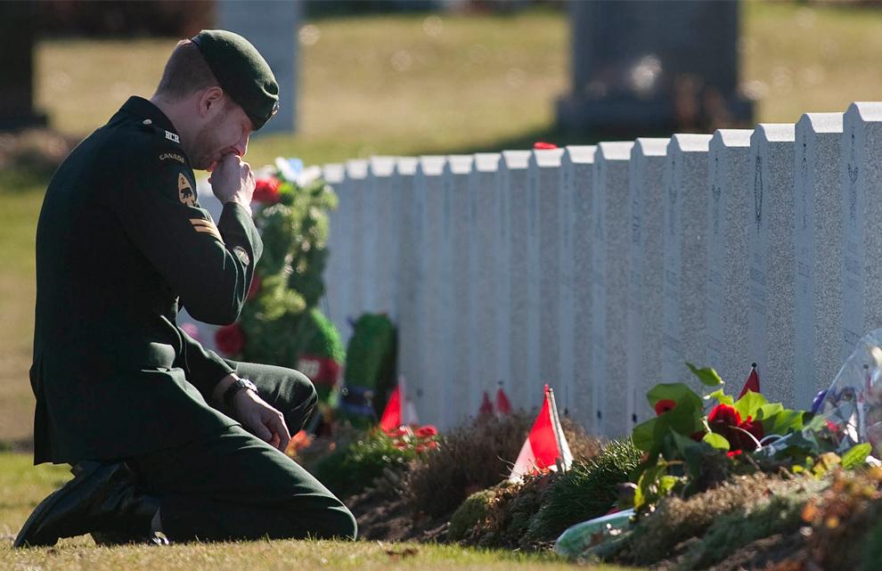 7. Солдат канадской армии у могилы на Национальном военном кладбище в День Памяти в Оттаве в среду 11 ноября 2009 года. (AP Photo/The Canadian Press, Pawel Dwulit)