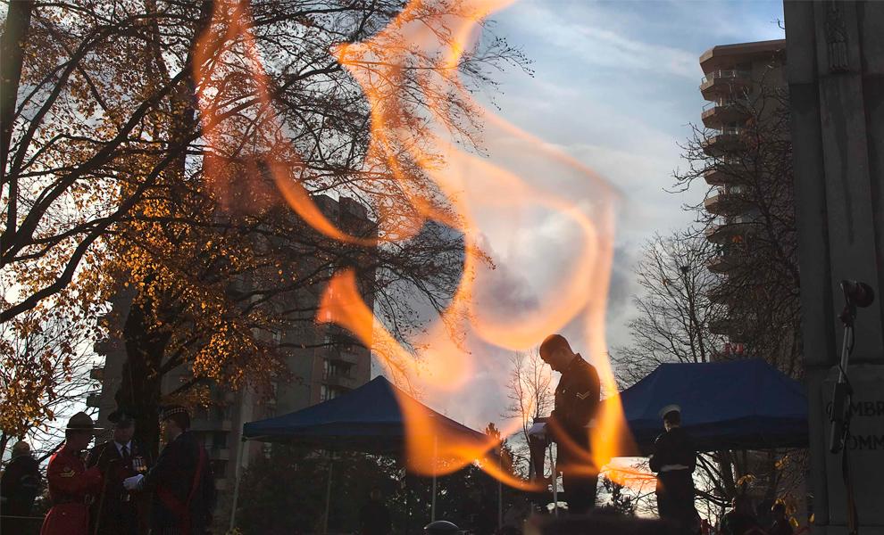 13. Канадский солдат, который стоит в карауле в военном мемориале, виден сквозь вечный огонь перед началом церемонии в честь Дня Памяти в Северном Ванкувере, Британская Колумбия, 11 ноября 2009 года. (REUTERS/Andy Clark)