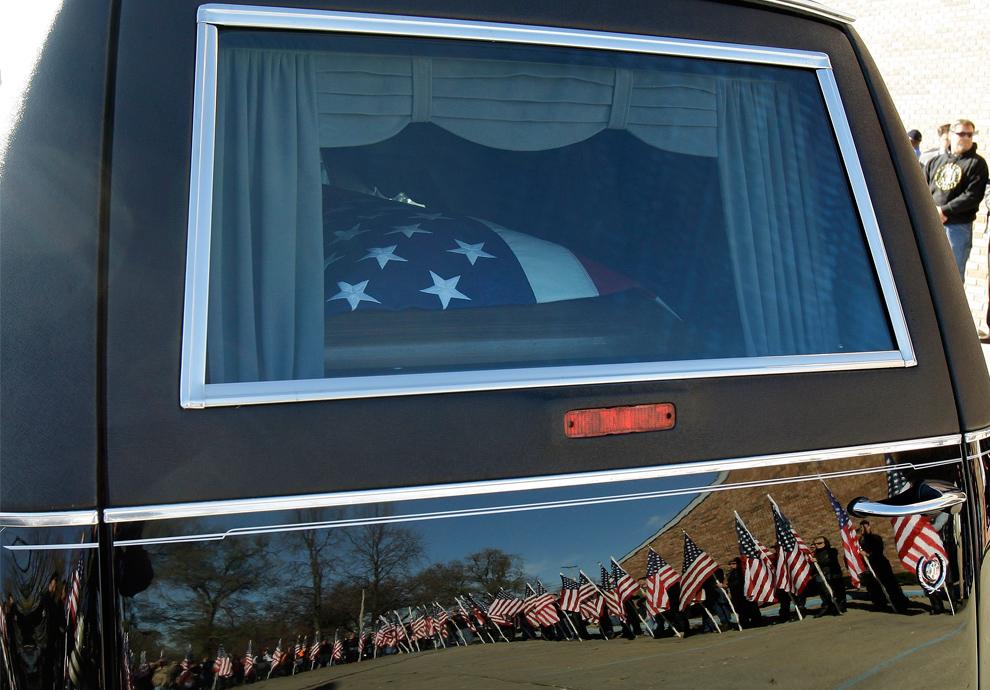 18. Покрытый национальным флагом гроб сержанта Дэйла Гриффина на катафалке перед началом поминальной службы Дня Ветеранов в Терре Хойте, штат Индиана, в среду 11 ноября 2009 года. Грифин погиб 27 октября в результате взрыва придорожной бомбы в Афганистане. (AP Photo/Darron Cummings)