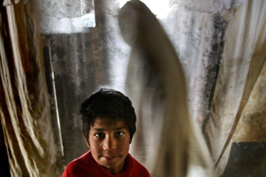 1) 8 летний Залмай ждет перед занавеской, которой закрыта дверь в камеру, где он уже четыре года живет вместе со своей матерью Паригуль, чье преступление заключается в том, что она сбежала из дома. Снимок сделан в тюрьме Пул-и-Чаркхи в Кабуле 17 апреля 2008. (AP Photo/David Guttenfelder)
