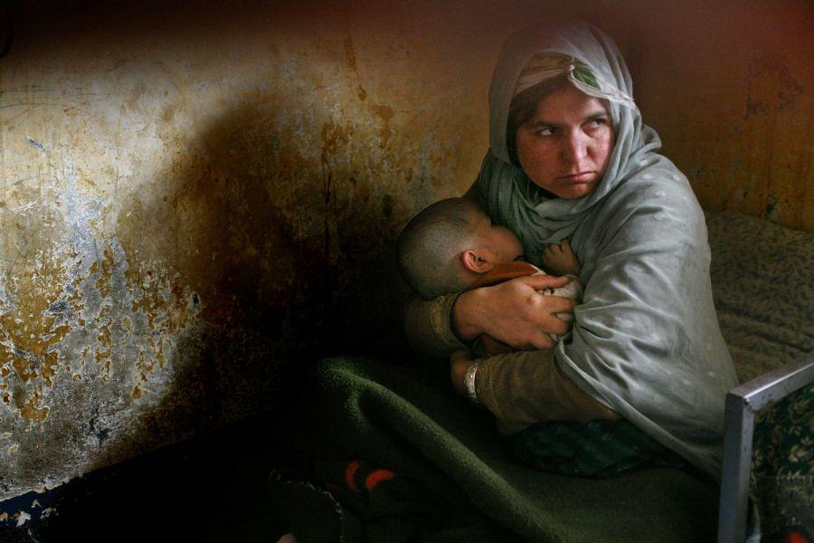 4) Хабиба, отсидевшая три года своего 10-летнего тюремного заключения за убийство, нянчит свою дочь Назанин, которая родилась в тюрьме три года назад, но до сих пор не умеет ходить. Снимок сделан в камере кабульской тюрьмы Пул-и-Чаркхи 17 апреля 2008. (AP Photo/David Guttenfelder)